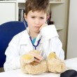 Serious child doctor at work with bear plush — Foto de Stock   #64409391