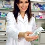 Pharmacist giving medicine to customer in pharmacy smiling — Stock Photo #65364755