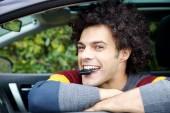 Happy man with key of new car in mouth smiling  — Stock Photo