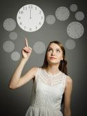 Girl pointing at a clock. — Stock Photo