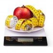 Apple with measuring tape on a digital kitchen scale — Stock Photo #66072829