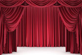 Open red theater curtain, lit by a spotlight — Stock Photo