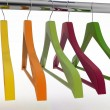 Row of color coat hangers on metal clothes rail — Stock Photo #62989085