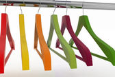 Row of color coat hangers on metal clothes rail — Stok fotoğraf