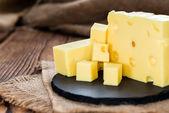 Block of Cheese on black  board — Stock Photo