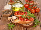 Bruschetta with tomatoes and arugula — Stock Photo