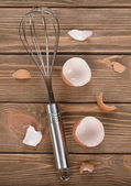 Whisk and eggshell — Stock Photo