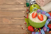 Oatmeal, strawberries and measuring tape — Stock Photo