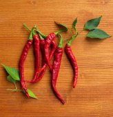Chili peppers on wooden background — Stock Photo