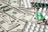 Hundred dollar bills and pills blisters close-up — Stock Photo