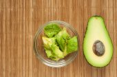Halved avocados on rustic wooden background — Stock Photo