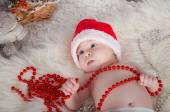 Cute baby in santa hat lying on the carpet near the Christmas tree — Stock Photo