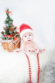 Cute baby in Santa's hat with a Christmas tree behind — Stock Photo