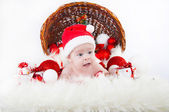 Funny baby dressed in Santa Claus hat on bright festive background — Stock Photo