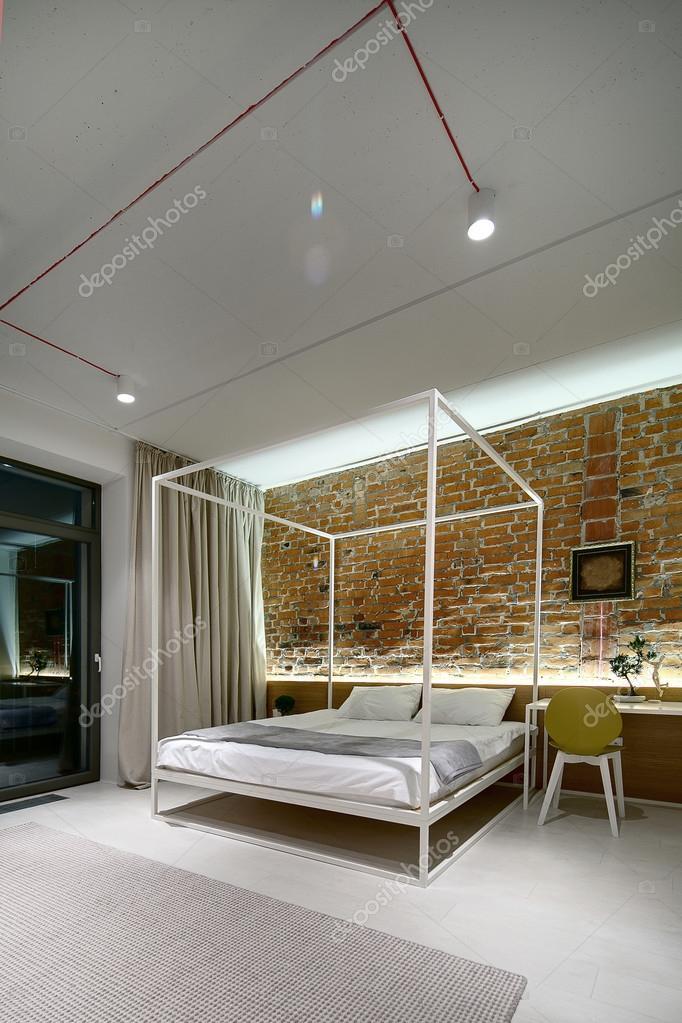 Chambre à coucher dans un style loft moderne. Mur de briques sans ...