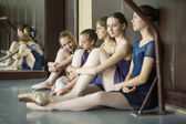 Five young dancers in the same dance costumes, resting sitting o — Foto de Stock