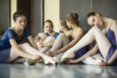 Five young dancers in the same dance costumes, resting sitting o — Stock Photo