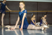 Ballerina sitting on the floor in the splits in a dance class da — Stock Photo