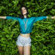 Young, attractive brunette lays back on the lush green foliage. — Stock Photo #64789351