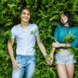 Young couple holding hands on the back is bright green foliage. — Stock Photo #64789383