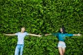 Young couple is closing his eyes back on the bright green foliag — Stock Photo