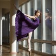 Graceful ballerina dancing in a purple dress leg lifted high, st — Stock Photo #65636757