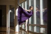 Graceful ballerina dancing in a purple dress leg lifted high, st — Stock Photo