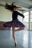 Long-haired ballerina spins in the dance moves on one leg to sta — Stock Photo