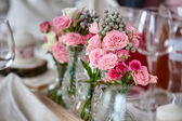 Bouquets of roses on a festive wedding table in the restaurant. — Stock Photo