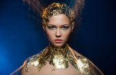 Close-up portrait girl model in a stylish gold foil. Blurred mar — Stock Photo