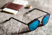 Stylish sunglasses with blue tinted mirror on textured wooden ba — Stock Photo