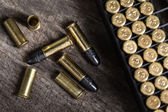 Scattering of small caliber cartridges on a wooden background — Stock Photo