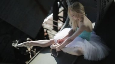 Blond dancer in a white tutu sits on the edge of bridge. — Stock Video