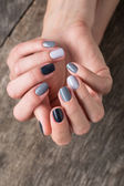 Beautiful hands with the miniature painted in a gray-colored nai — Stock Photo