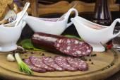 Salsichas numa placa de madeira com legumes — Fotografia Stock