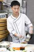 Japanese chef in restaurant making sushi rolls — Stockfoto