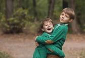 два брата huging друг друга открытый — Стоковое фото