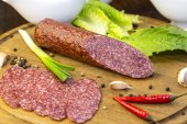 Sausage on wooden plate — Stock Photo