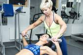 Athletic woman working out with trainer — Stock Photo