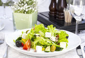 Greek salad on a table — Stock Photo