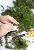 Woman affixing branches on Christmas wreath — Stock Photo