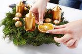 Woman attaches orange on Christmas wreath — Stock Photo
