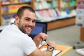 Portrait of a man with glasses in a bookstore — Stock Photo