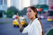 Latina businesswoman calling taxi car leaving work — Stock Photo