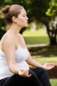 Pregnant woman mother belly relaxing park yoga lotus — Stock Photo