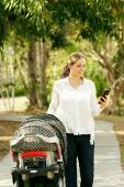 Mother With Baby In Pushchair Sending Message On Phone — Stock Photo