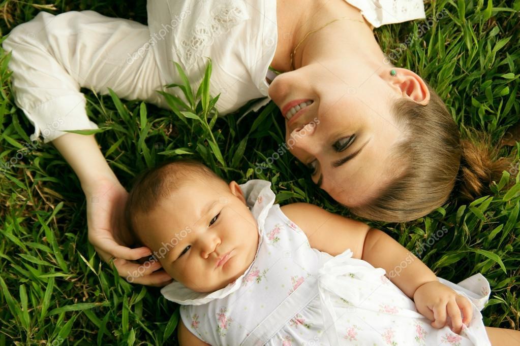Madre con hija tendido sobre la hierba de caricias � Foto stock ...