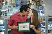Happy Shop Owners kissing And Showing First Dollar — Stock Photo