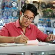 Chinese Man Working In Computer Shop Checking Bills And Taxes — Stock Photo #71359613