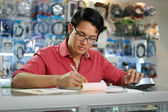Chinese Man Working In Computer Shop Checking Bills And Taxes — Stock Photo